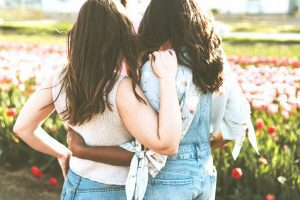 two girls stand with each other - true friends signs