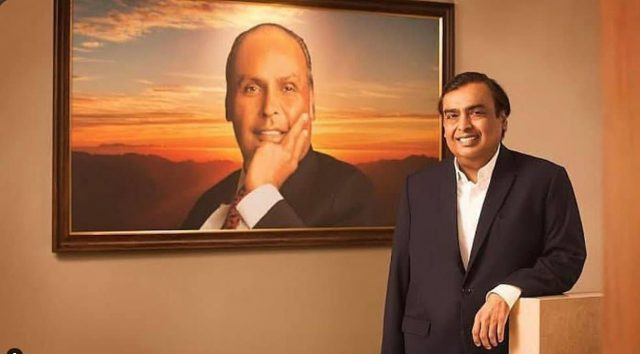 Mukesh ambani with pic of dheeru bhai ambani